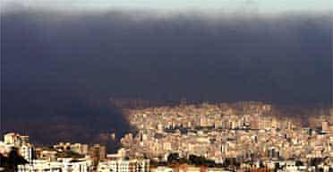 Smoke from burning tyres and debris hangs over Beirut as thousands of demonstrators enforcing a general strike aimed at toppling the government brought much of Lebanon to a standstill. Photograph: Hussein Malla/AP
