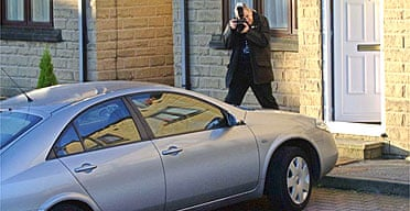 A police officer photographs a car outside a Halifax address after anti-terror raids in the area