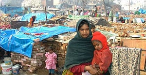Puja, seen with her child Arun, standing in front of the ruins of her home at Shankar Garden in west Delhi. She claims her newborn baby was killed during the demolition of her house by the Municipal Corporation of Delhi.