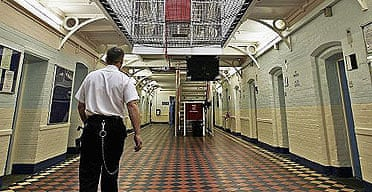 A prison officer walks through a wing of Norwich prison.
