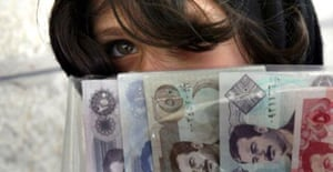 An Iraqi refugee in Amman makes ends meet by selling Iraqi banknotes issued under Saddam Hussein to tourists