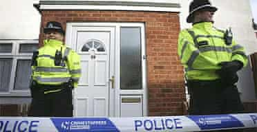 British police officers stand outside a house in Birmingham