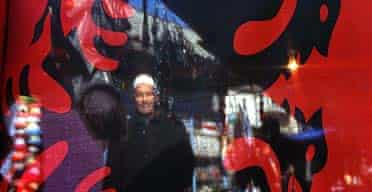 A Kosovo Albanian stands behind the Albanian national flag at a market in Pristina