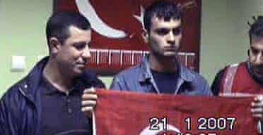 A video still showing Ogun Samast, who has confessed to the murder of Hrant Dink, holding a Turkish flag next to security officials
