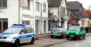 Police officers secure the area in front of the Chinese restaurant in Sittensen where six bodies were found shot dead