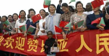 Members of Zambia's Chinese community wait to greet their country's president, Hu Jintao, at Lusaka international airport