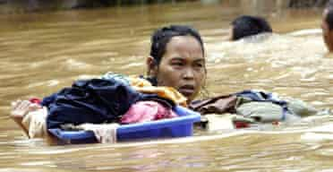 An Indonesian woman struggles through floodwaters with her belongings in Jakarta