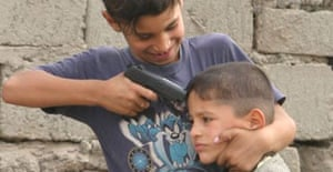 Iraqi boys in a refugee camp in Baghdad play with toy guns