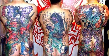 Three men show off their tattoos, heavily associated with Japanese gangsters, or yakuza