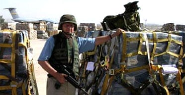 An armed guard poses beside pallets of $100 bills in Baghdad
