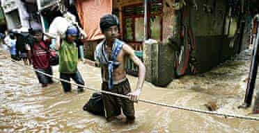 Residents of Jakarta make their way along a flooded street after fresh rain brought further misery to the Indonesian capital