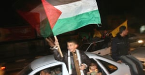 A boy waves a Palestinian flag as people in Gaza city celebrate the agreement between Hamas and Fatah to form a government of national unity