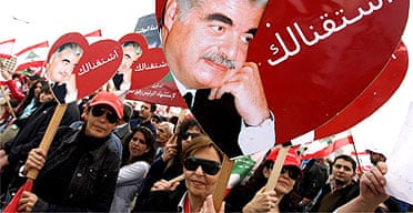 Demonstrators carry pictures of former Lebanese prime minister Rafiq Hariri in Beirut on the second anniversary of his assassination