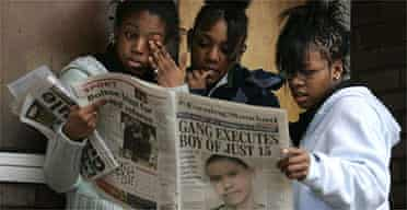 Children read a newspaper with a picture of murdered 15-year-old Billy Cox on the front page