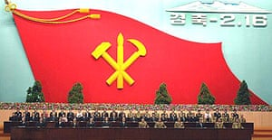 Delegates at a ceremony to mark the 65th birthday of Kim Jong Il, with a giant flag of North Korea's ruling Korean Workers' party in the background.