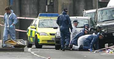 Police officers examine the scene in Hackney where a man was shot dead