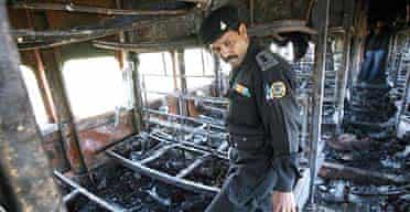 An Indian national security guard inspects the charred carriages of the Samjhauta Express