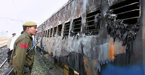 A police officer looks at a burnt-out carriage of the Samjhauta Express