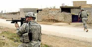 A US army soldier provides cover fire for a fellow serviceman during a raid in Buhriz, about 35 miles north of Baghdad, Iraq