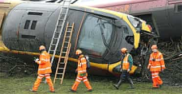 Rail workers walk past the derailed Virgin Express