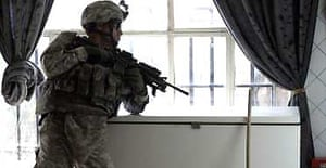 A US soldier takes a break during a search of an apartment in the south-east of Baghdad. Photograph: Carlos Barria/Reuters