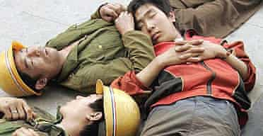 Exhausted migrant workers nap together during a lunch break on a construction site in Beijing, China.