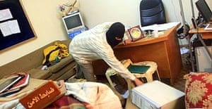 A masked officer collected his belongings from an intelligence office in Basra, raided overnight by Iraqi special forces