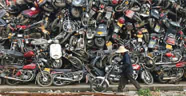 A worker pushes parts of a motorcycle at a scrapyard in Guangzhou, southern China.