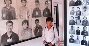 A Cambodian student looks at photographs of Khmer Rouge victims the genocide museum in Phnom Penh
