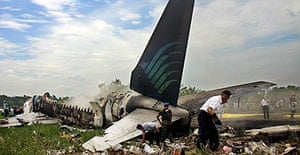 Rescue workers inspect the wreckage of a Boeing 737-400 jet of Garuda Indonesia airlines in Adisucipto airport, Yogyakarta.