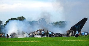 Indonesian investigators look at the wreckage of a Garuda airlines plane at Yogyakarta international airport
