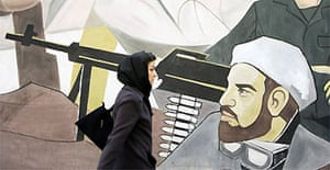 A woman walks past a mural on a wall at Palestine Square in Tehran, Iran