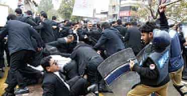 Pakistani police officers hit lawyers with batons during a rally to protest the sacking of the country's top judge