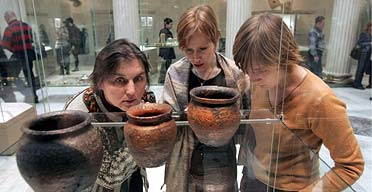 Visitors to the Pushkin museum examine the exhbition, which includes pottery, necklaces, and brooches with runic inscriptions