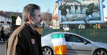 Sinn Fein president Gerry Adams passes a republican mural in the Ballymurphy area of Belfast , Northern Ireland.