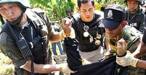 Thai policemen carry the body of one of nine minibus passengers who were shot dead by separatist insurgents in southern Thailand