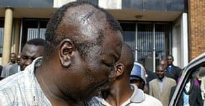 Opposition leader Morgan Tsvangirai shows his wounds outside the court
