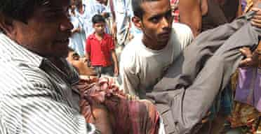 A man with a bullet wound is carried to hospital in the Indian town of Nandigram