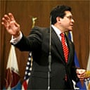 Alberto Gonzales attends a press conference at the justice department headquarters