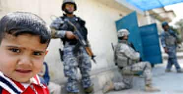 An Iraqi boy stands next to US soldiers and members of Iraq's national police in on patrol in Baghdad