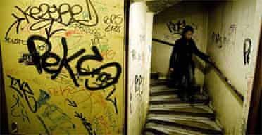 Natalie Kouyate walks down the graffiti-covered stairwell of the block of flats where she lives on La Forestière estate, Clichy sous Bois, where the 2005 riots originated