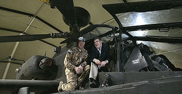 Gordon Brown sits on an Apache helicopter gunship with Major Paul Tennant of the 664 Squadron, 9 Regiment, of Army Air Corps, while visiting British troops in Afghanistan.