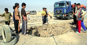 Iraqi children inspect a crater caused by a roadside bomb which killed four British soldiers in Basra