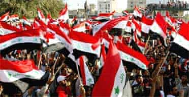 Iraqi Shia supporters of Moqtada al-Sadr wave the Iraqi national flags during an anti-US rally in Najaf