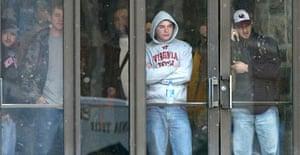 Virginia Tech students watch from the doorway of McBryde Hall on the Virginia Tech campus in Blacksburg