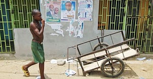 A boy walks past election campaign posters in Nigeria