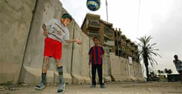 Boys play football near a blast wall in Baghdad