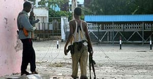 Two Islamist insurgents hide behind a wall in Fagah neighbourhood, north of Mogadishu, where Ethiopian troops and Islamists are fighting