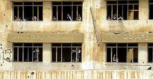 Iraqi girls play in the ruins of a school in Fallujah