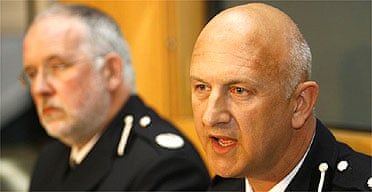 Kent police assistant chief constable Adrian Leppard (r) addresses the media after animal rights activism raids